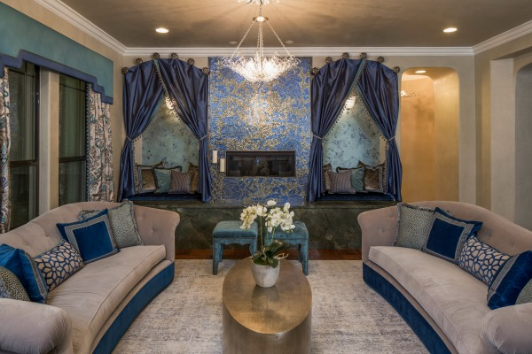 this colorfully styled guest house features a beautiful blue hued living area that invites conversation the fireplace boasts a delicately designed mural